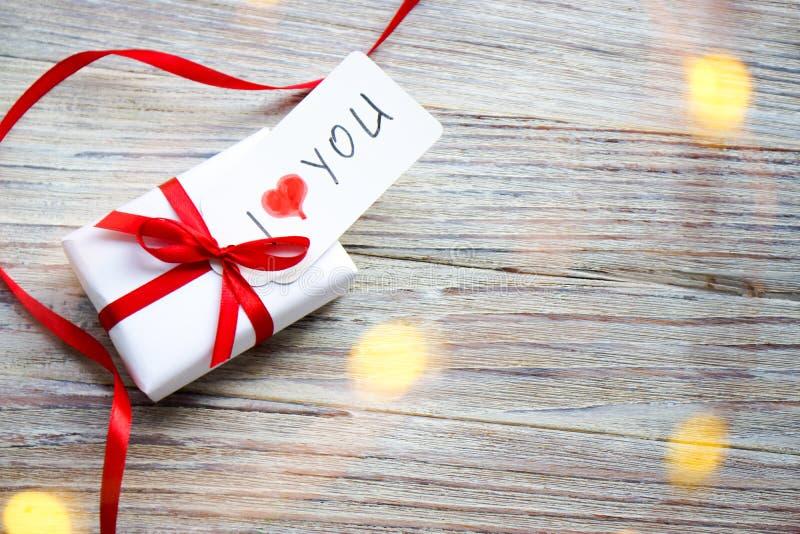Белая подарочная коробка с красным смычком и сердца на белой деревянной предпосылке с bokeh золота, подарком дня Святого Валентин стоковое изображение rf