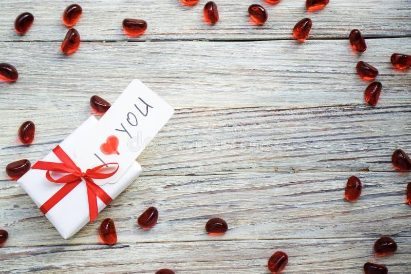 Белая подарочная коробка с красным смычком и сердца на белой деревянной предпосылке с bokeh золота, подарком дня Святого Валентин стоковая фотография