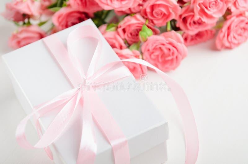 Белая подарочная коробка с розовой лентой и букет роз на белой предпосылке Подарок на день Валентайн, день рождения стоковые фото