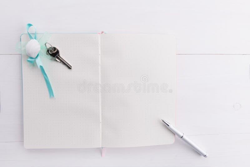 Белая пустая страница тетради, ручки и домашнего ключа на белой деревянной предпосылке с космосом экземпляра, концепцией строгать стоковые фотографии rf