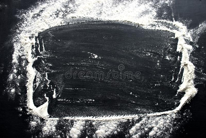 Белая пшеничная мука разбросана на черную таблицу стоковые фото