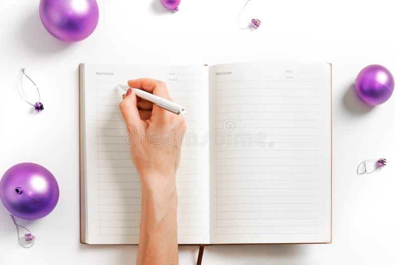 Белая рука блокнота предпосылки писать разрешению Нового Года жизнь фиолетового шарика планируя умные цели стоковые фото