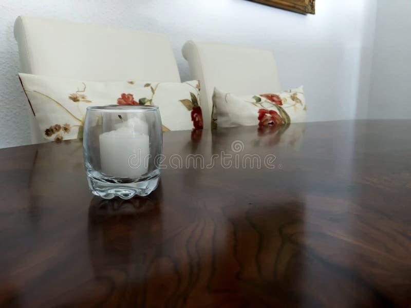 Белая свеча на деревянном столе с белыми стульями стоковые изображения rf