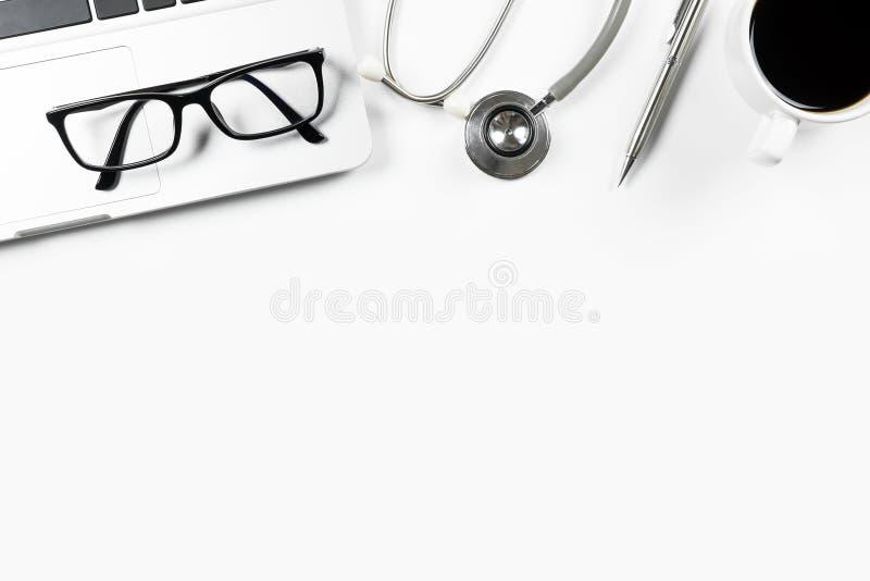 Белая современная таблица стола ` s доктора с стетоскопом, кофейной чашкой и поставками Взгляд сверху с космосом экземпляра, плос стоковое фото