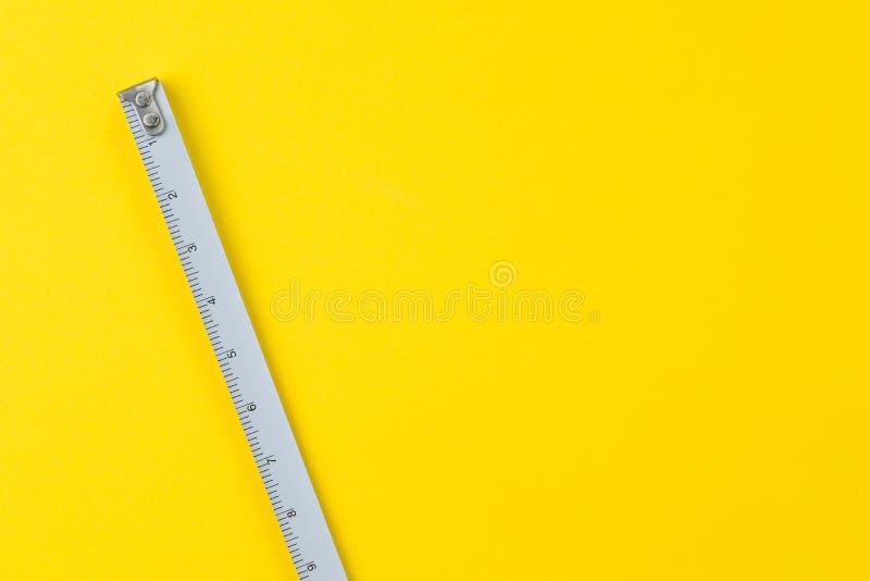 Белая стальная рулетка с сантиметром и дюймами на яркой желтой предпосылке с концепцией космоса, длины, длинных или создателя экз стоковые изображения rf