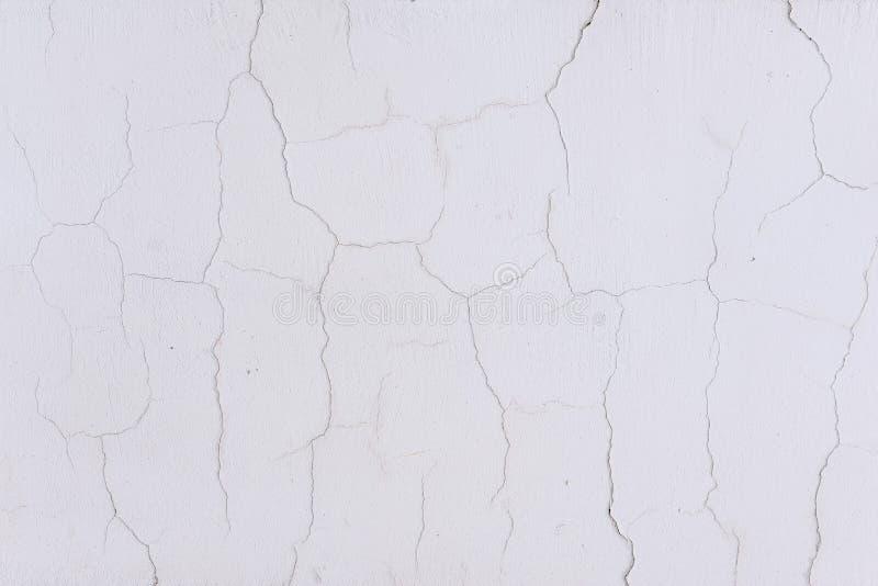 Белая стена треснула Старые городские стены Текстура старой стены Поверхность цемента покрасила с белой краской Архитектура и стоковая фотография