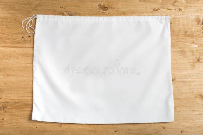 Белая сумка мешка на строках на деревянной предпосылке, насмешливой вверх стоковое изображение