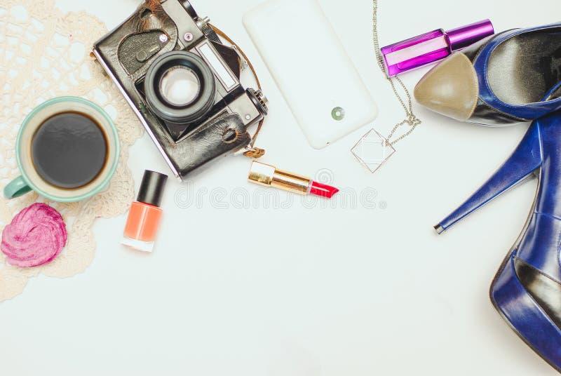 Белая таблица стола офиса с smartphone, винтажной камерой, кофе, ботинками ` s женщин и косметиками стоковое фото