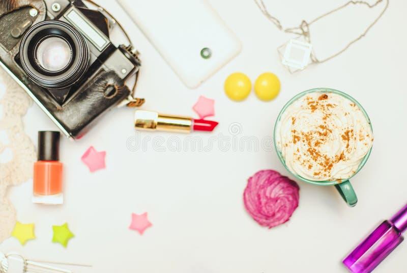 Белая таблица стола офиса с smartphone, винтажной камерой, latte специи и косметиками стоковое фото rf