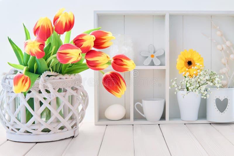 Белая таблица с красными и желтыми тюльпанами и украшением весеннего времени стоковое изображение