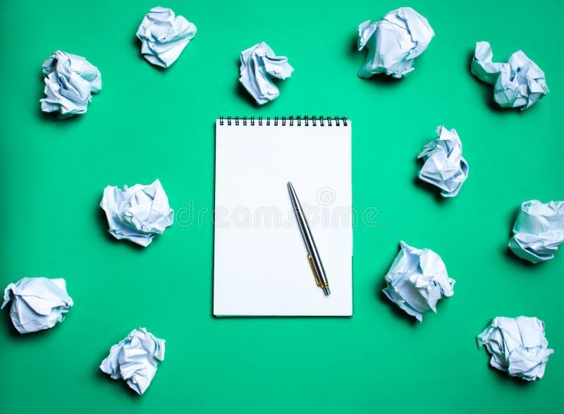 белая тетрадь с ручкой на зеленой предпосылке среди бумажных шариков Концепция производить идеи, изобретая новые идеи Бумажные ша стоковые изображения