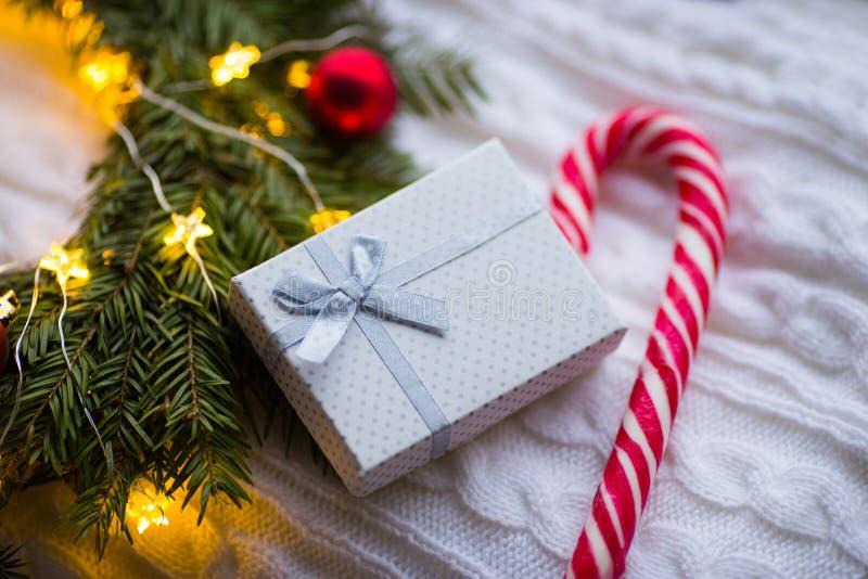 Белая тросточка подарочной коробки и карамельки около венка ели с красными шариками рождества и свернутого спиралью с накаляя гир стоковые фото