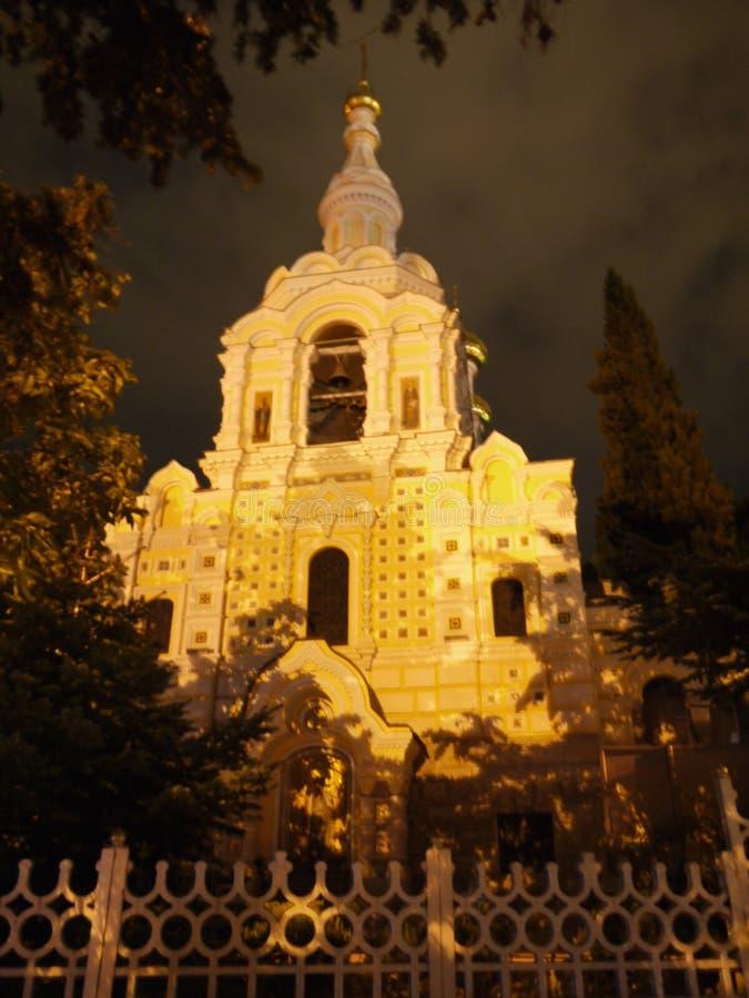 Белая церковь затоплена с яркими лучами солнца от одной стороны и хмурым небом от другой стороны Интересы природы стоковое фото rf