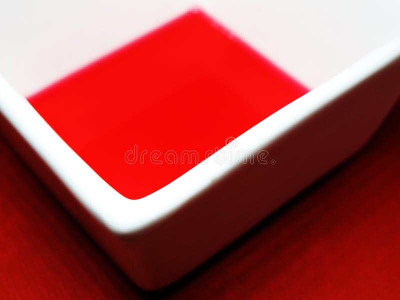 Белая чаша с красной жидкостью на красном фоне стоковое изображение