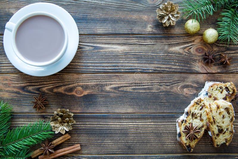 Белая чашка горячего шоколада с рождеством stollen торт на коричневой таблице, золотом pinecone и шариках рождества, космосе для  стоковые изображения rf