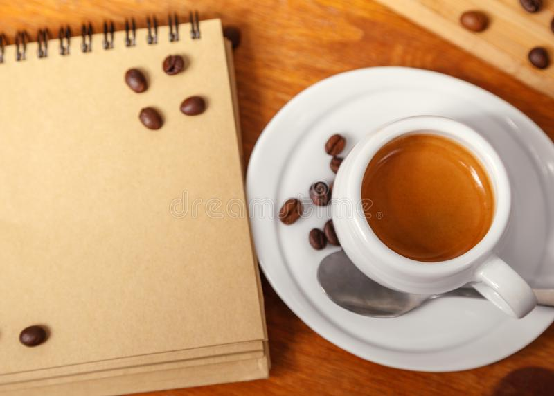 Белая чашка душистого кофе эспрессо с пеной и пусковой площадки сочинительства, разбросанных кофейных зерен на деревянном столе,  стоковая фотография rf