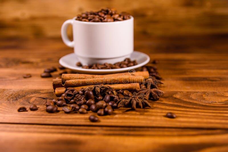 Белая чашка, наполненная кофе-бобами, звездным анизом и кориными палкаРстоковое изображение rf