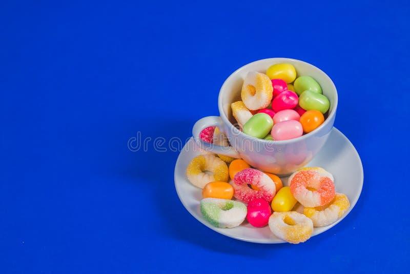 Белая чашка при сладостная конфета изолированная на голубой предпосылке Закройте вверх по выбору сортированной красочной конфеты  стоковое изображение rf