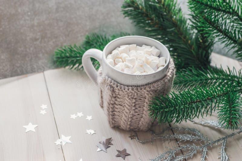 Белая чашка с зефирами в теплой связанной куртке на светлой деревянной предпосылке с рождественской елкой и серебристыми звездами стоковое фото