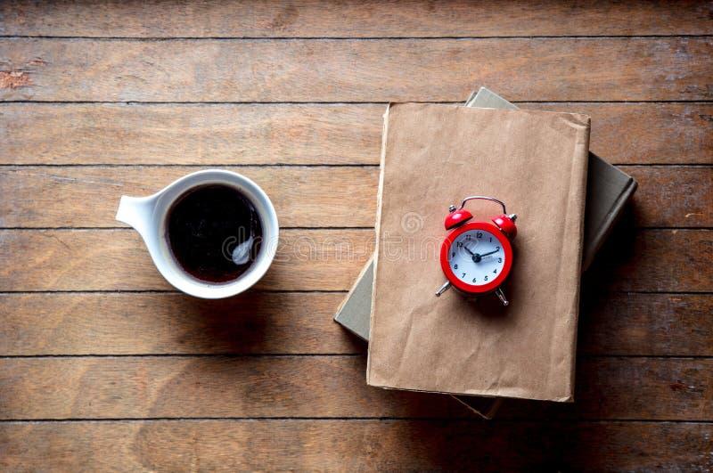 Белая чашка с кофе и книгами с будильником стоковое изображение