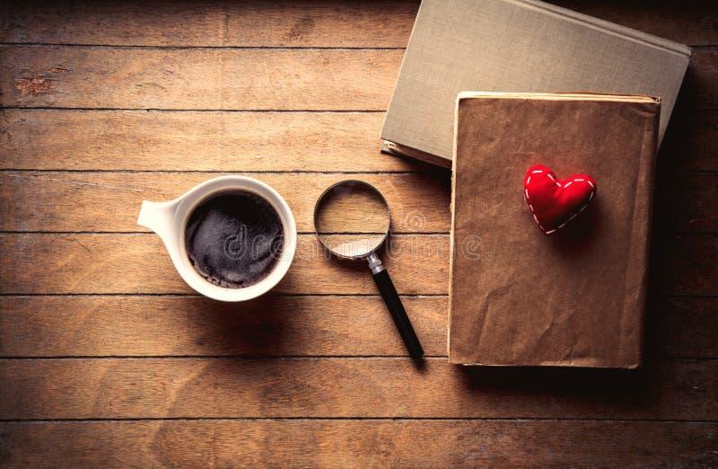Белая чашка с кофе и книгами с увеличителем стоковая фотография