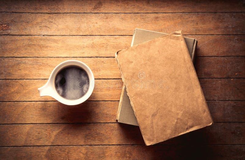 Белая чашка с кофе и книгами стоковые фотографии rf