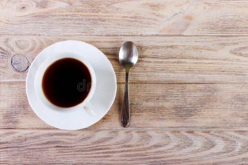 Белая чашка с кофе на диске и ложке на деревянной предпосылке стоковое изображение