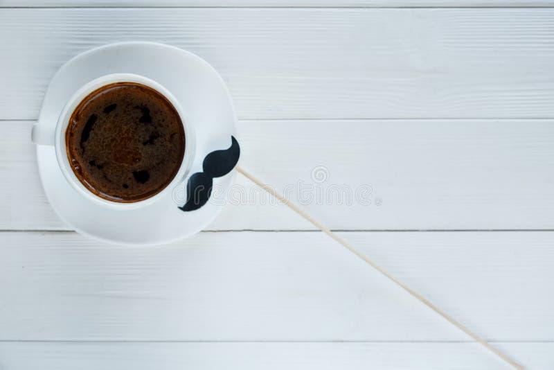 Белая чашка с кофе усик около его на белой предпосылке Осведомленность рака предстательной железы, осведомленность здоровья людей стоковая фотография rf
