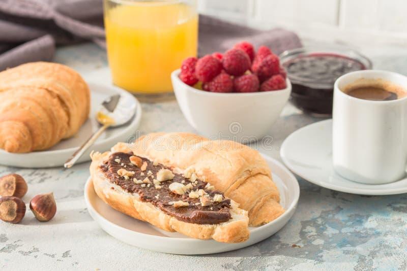 Белая чашка черного чая с круассаном или здравицами с арахисовым маслом, затиром chokolate, студнем или вареньем на белом деревян стоковое фото