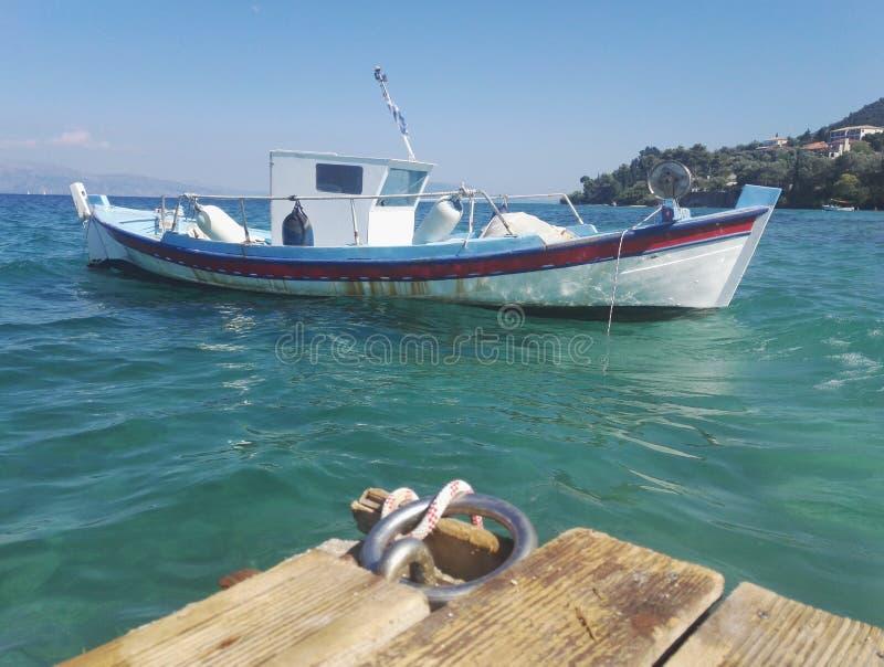 Белая шлюпка плавая на голубое море стоковая фотография rf