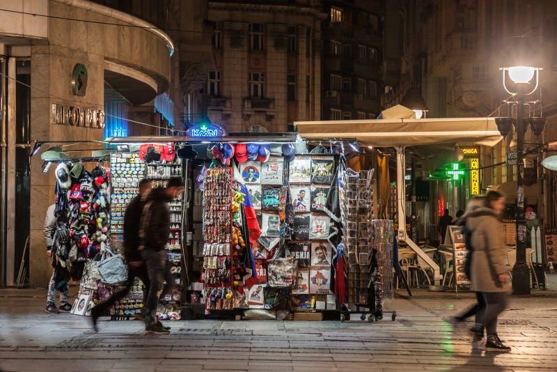 БЕЛГРАД, СЕРБИЯ - 25-ОЕ МАРТА 2018: Люди проходя перед сувенирным магазином на толпить улице Kneza Mihailova вечером стоковое фото