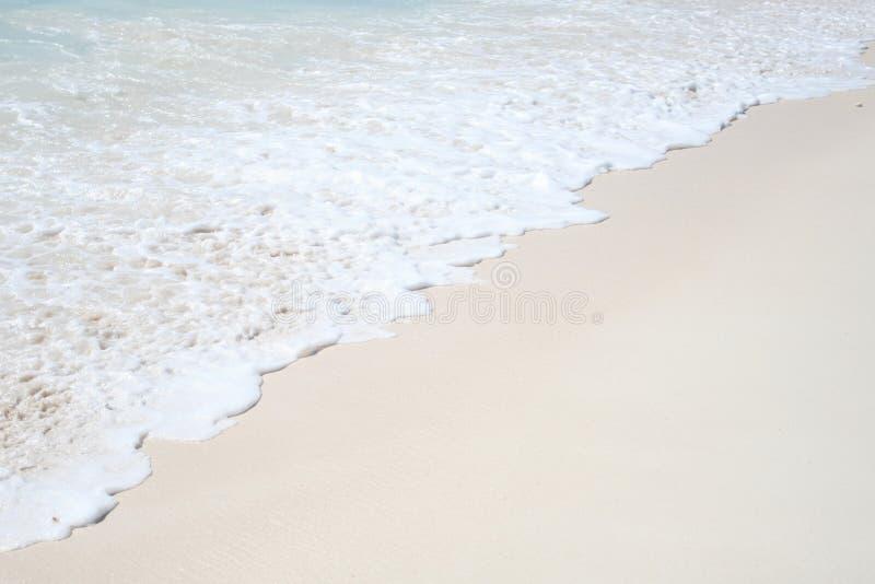 белизна волны песка завальцовки пены пляжа стоковые изображения