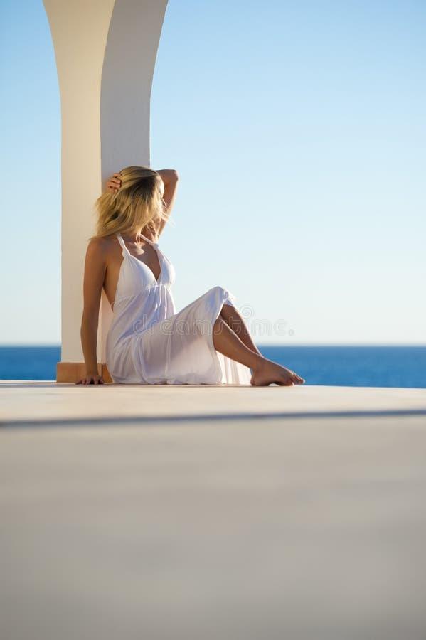 белизна захода солнца моря девушки платья стоковая фотография rf