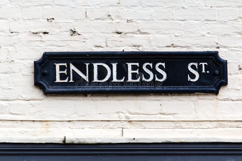 Белизна знака улицы на черно- бесконечной улице стоковая фотография rf