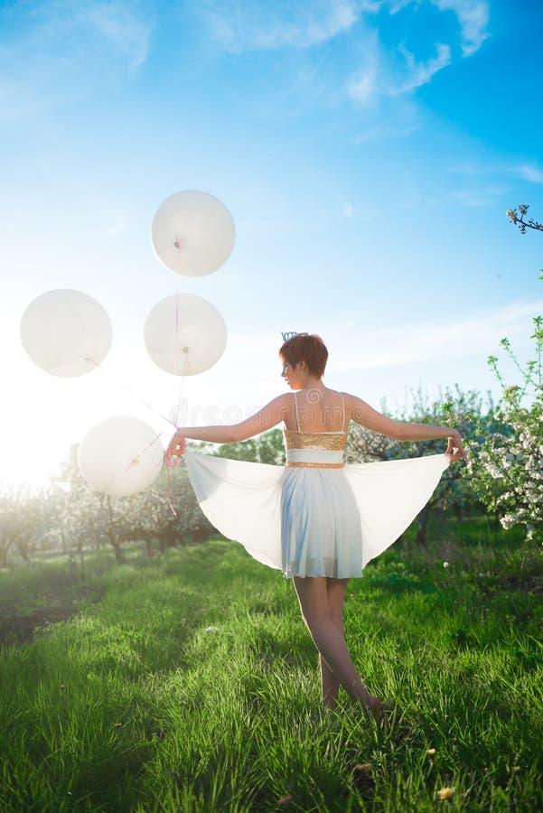 Белизна одела девушку идя в зеленый сад стоковые фотографии rf