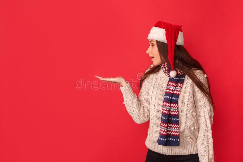 белизна торжества изолированная принципиальной схемой В сторону удивленная молодая женщина в положении шарфа и шляпы santa на кра стоковые изображения