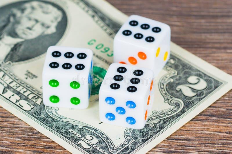 Белизна dices с красочными точками и 2 долларами банкноты стоковая фотография rf