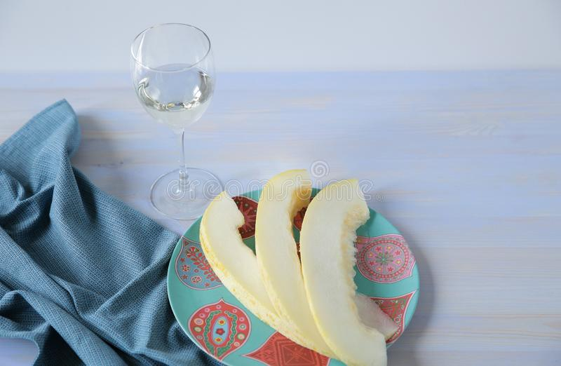 Белое вино в стеклянной и зрелой желтой сладкой дыне отрезало в плите стоковые изображения