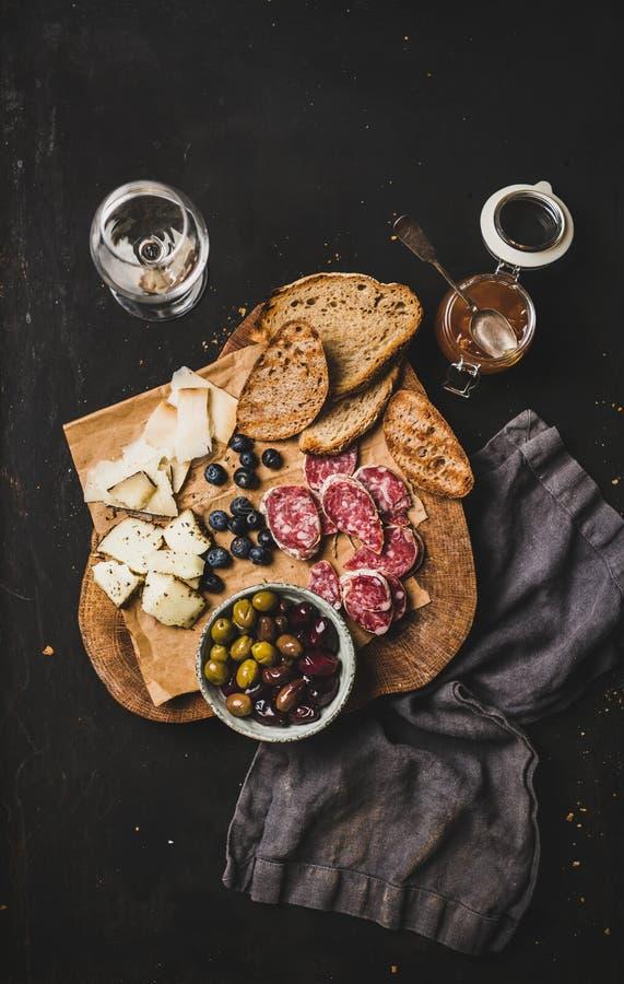Белое вино и закуски на черном фоне, вид сверху стоковое изображение rf