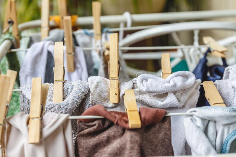 Белое и покрашенное белье, который нужно высушить на веревке для белья с деревянными зажимками для белья стоковое изображение