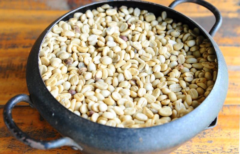 Белое кофейное зерно в винтажном стальном ведре на деревянном столе стоковые фотографии rf