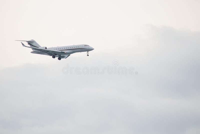 Белое летание самолета против белого неба стоковые изображения rf