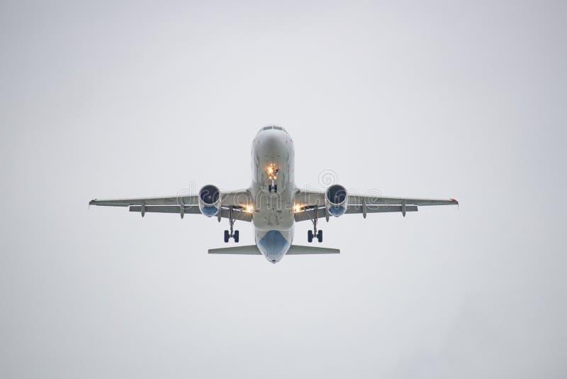 Белое летание самолета против белого неба стоковое фото