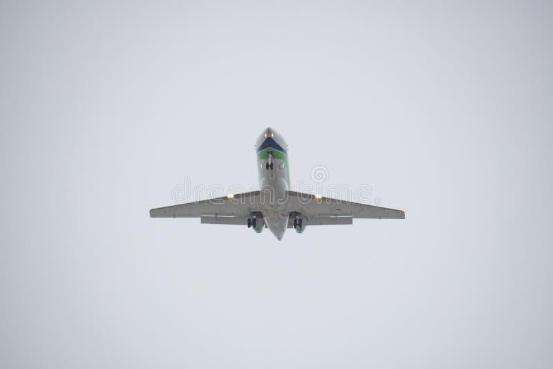 Белое летание самолета против белого неба стоковая фотография rf