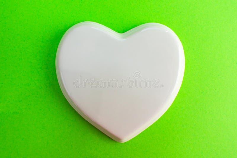 Белое лоснистое сердце фарфора к зеленой фиолетовой предпосылке; свадьба; Карта свадьбы; Примечание любов стоковые фото