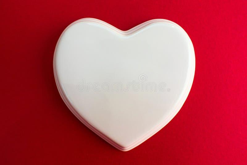 Белое лоснистое сердце фарфора к красной фиолетовой предпосылке; свадьба; Карта свадьбы; Примечание любов стоковые изображения