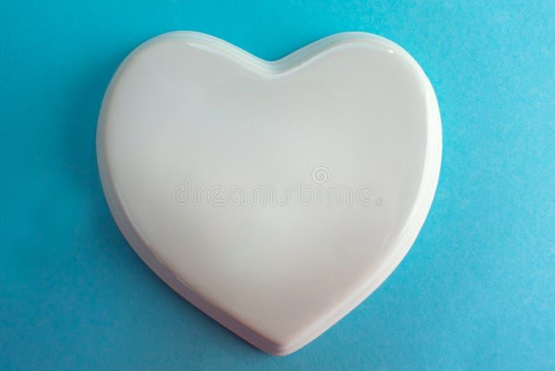Белое лоснистое сердце фарфора к светлому - голубая предпосылка; свадьба; Карта свадьбы; Примечание любов стоковая фотография rf