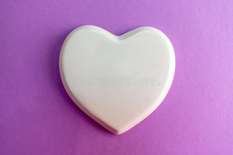 Белое лоснистое сердце фарфора к светло-фиолетовой предпосылке; свадьба; Карта свадьбы; Примечание любов стоковое изображение