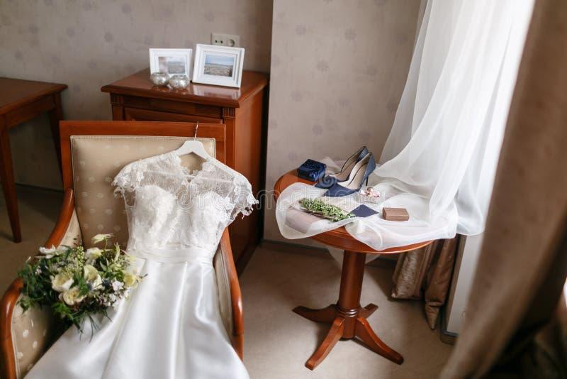 Белое платье свадьбы при шнурок лежа на стуле цветки букета различные Современный bridal пук с цветком мака и стоковые изображения rf