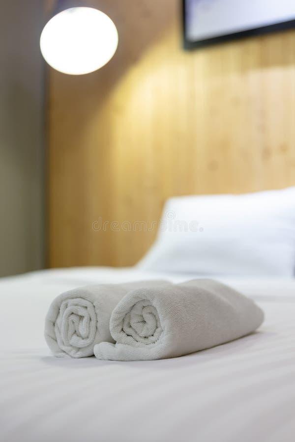 Белое полотенце на кровати в номере для клиента отеля стоковое фото rf